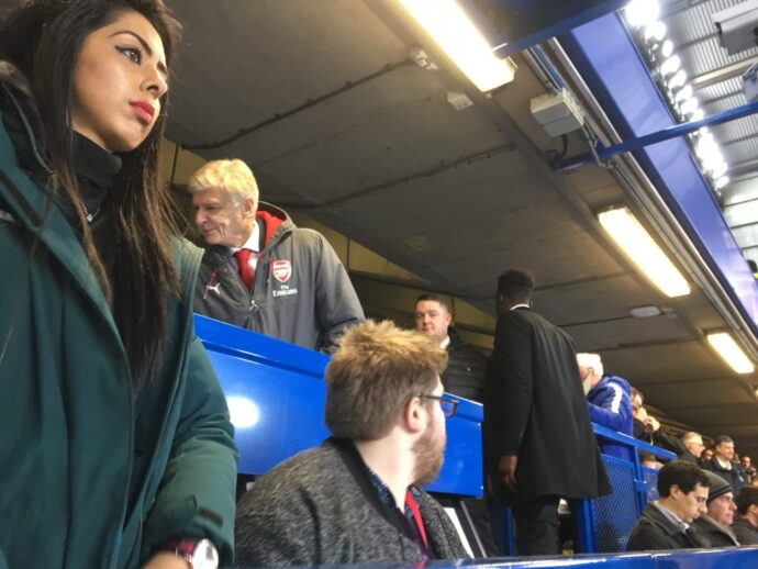 The Arsenal manager resumes his seat in the press box after half-time