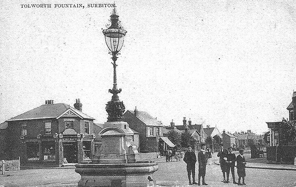 Lads by the fountain. The shop to the left, at the corner with Beaconsfield Road, is now Jezzards estate agent
