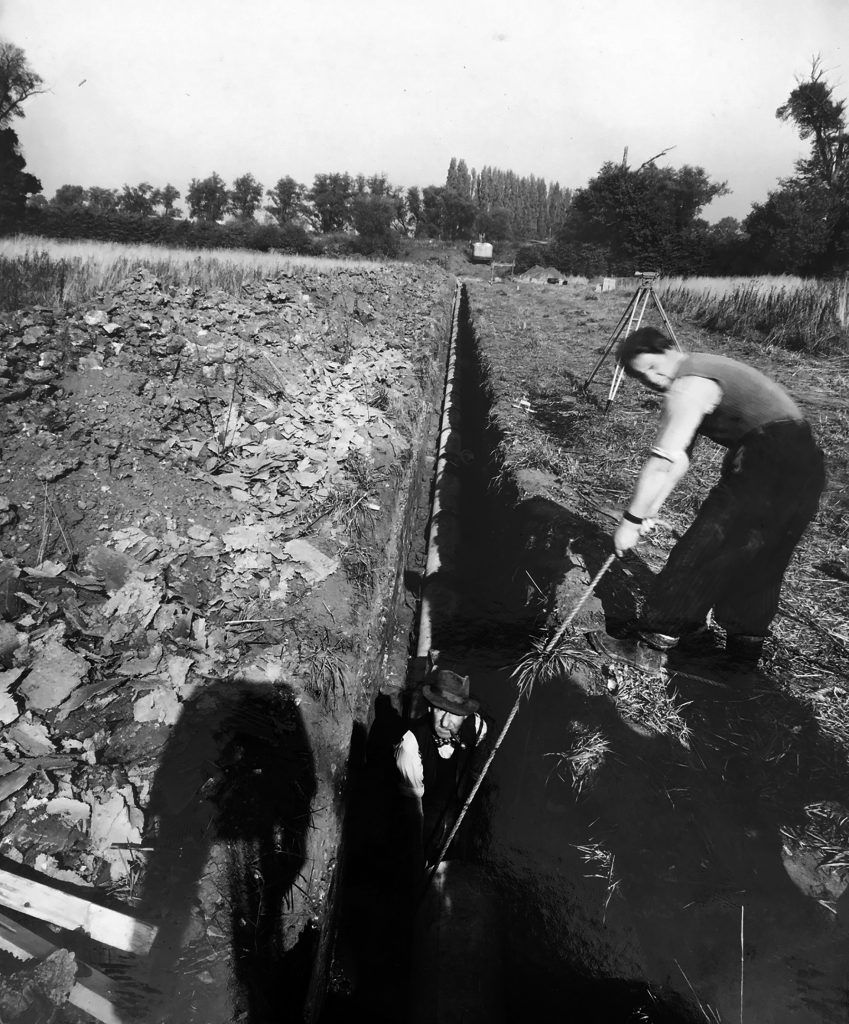 1953 workmen in hats and bow ties (and smoking pipes) dig the drainage ditches